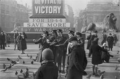 London, 1944: Members of the Women's Auxiliary Air Force (WAAF) and children are amongst those feeding the pigeons in Trafalgar Square in London. In the background, the base of Nelson's Column is covered in War Savings posters and one of the Trafalgar Square lions can also be seen.