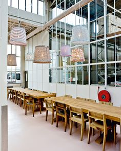 Dutch designer Piet Hein Eek found an abandoned factory space on the outskirts of Eindhoven, and converted it into his studio, shop, gallery, restaurant, event room, factory, and atelier for designers. The dining area, with pendant lamps made using Paul Smith fabrics.
