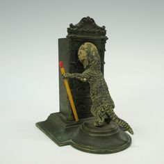 GREAT antique cold painted Vienna bronze match striker holder featuring a cat looking closely at the time on a Grandfather type clock. The paint is