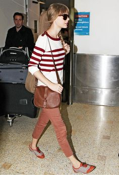Taylor Swift wears a red and white striped sweater, skinny jeans, oxfords, and a leather shoulder bag