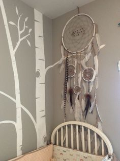 Handmade dream catcher we made for Wesley's nursery. I just love how this turned out! Used inner wooden hoop from sewing/stitching hoops wrapped with hand ripped cotton, leather wrapped feathers and hemp woven centers with assorted wooden beads.
