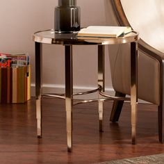 This glamorous, high-shine side/ end table evokes New York style with it's art deco spindles and tapered legs. A metallic gold frame pairs with a sleek tempered glass tabletop to display art, books, or vases full of flowers.