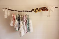 Gosh I love this branch displaying baby's clothes and shoes.