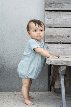 Adorable soft wrap suit for baby in dusty blue Gauze. Elastic in legs for puffy look. Wrap opens with a pushbutton inside and visible string-closure by left side.
