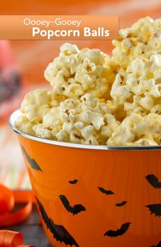 This Halloween, enjoy these Oooey-Gooey Popcorn Balls. Made with marshmallow coated popcorn, they're perfect as a snack or for trick-or-treating!