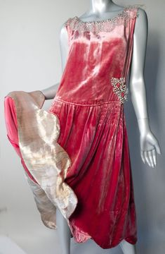 "1920s Dress of Gold Lame and Silk Velvet with Paste Appliques  Dress from the early 1920's, made from dusty rose colored silk velvet, has full gathered skirt with ruching at the sides. Measuring 5"" longer in the back, the scalloped hem is lined in 12"" of lame - the color of which can best be described as worn white gold, echoed also by the paste and metallic appliques at the waist and the metallic lace collar of the same color. Front Detail 5"