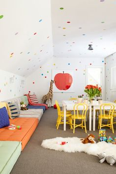 In the house's third-floor attic, the kids can let loose in the playroom strewn with tufted floor pillows. Instead of wallpaper, Simonpietri used hundreds of polka-dot decals from Urban Walls to create a one-of-a-kind motif. The framed apple on the wall is by artist Enzo Mari, the fluffy sheepskin throw is from Chango & Co.'s shop, and the miniature bistro chairs are by Pottery Barn Kids.