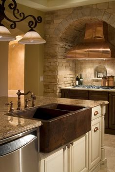 custom kitchen featuring copper range hood with hammered copper farm sink  www.imyourbuilder.com