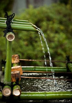 Shishi-odoshi: water-filled bamboo tube which clacks against a stone when emptied; device for scaring birds from gardens in Japan.