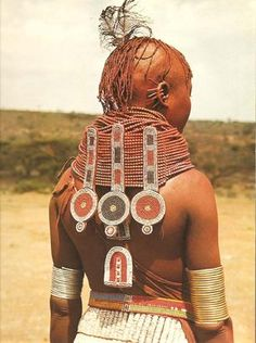 "Africa | ""Turkana men say of a lovely woman, 'It is the things she wears that make her beautiful.' When a young girl is ready for marriage she covers her body with ochre and fat, wears and elaborate bead pendant necklace and an ostrich feather in her hair. An ostrich eggshell belt, n'gakirim, holds up her long beaded skirt."" 
