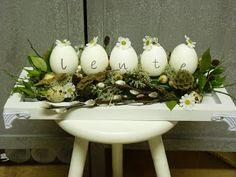 Ik heb met een watervaste stift op de eieren de letters geschreven. Ze daarna opgeplakt op een reep oasis, die volgestoken met katjes, groen etc. De witte kamille zijn zijden bloemetjes dus het stuk kan de hele lente blijven staan.