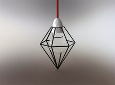 A crystal shaped black wire frame lamp. The industrial style shade is made to be flexible at the top, so that a light bulb can be inserted, these flexible