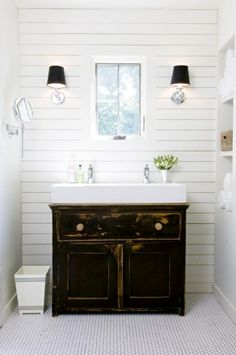 modern cottage bathroom, distressed black painted rustic washstand chest for vanity; chrome wall sconces; horizontal wood paneling; penny tile on the floor