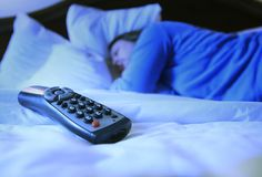 Woman sleeping in blue light from TV