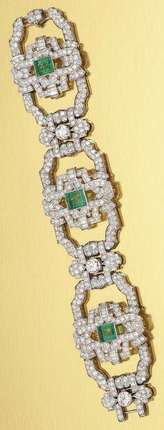 AN ART DECO EMERALD AND DIAMOND BRACELET, 1930S. Designed as a series of openwork geometric links millegrain-set with circular-cut and baguette diamonds, each alternately set to the centre with a collet-set step-cut emerald and circular-cut diamond respectively. #ArtDeco #bracelet