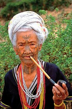 Myanmar/Burma | Portrait of a Chin lady with traditional tattoos, smoking a pipe | ©www.allmyanmar.com