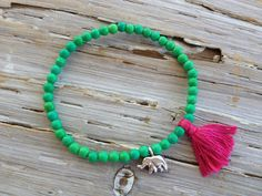 """$48 - GREEN CHALK TURQUOISE GANESHA BRACELET    It's hard not to get charmed by this bracelet. Vibrant green chalk turquoise a bright pink tassel and a sterling silver ganesha charm come together to create a perfect accent bracelet. Stretch bracelet measures 7"""", sized to fit most wrists."""
