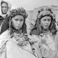 - Besancenot Jean (1902-1992) - Jeunes femmes des Ida ou Zekri aux visages tatoués. Elles portent les boucles d'oreilles, tikhorsin, passées dans le lobe de l'oreille mais également soutenues par une attache au bandeau de tête. Le collier tour de cou est fait d'une enfilade de grosses bagues. Elles ont sur la tête la toukaït sur laquelle repose soit la taounza, le diadème, soit une volumineuse couronne obtenue par une quantité de laines vivement colorées. - Arago