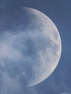 Daylight Photo of International Space Station Silhouetted in Front of Moon