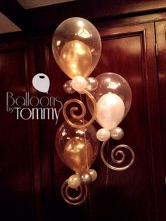This elegant and whimsical design is a crowd favorite. A bouquet of clear balloons with your event colors inside and a matching swirl base! | Balloons by Tommy | #balloonsbytommy