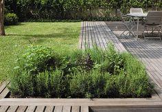 Com o desnível do terreno, a horta é logo avistada por quem adentra o jardim. Foi instalada em uma caixa de tábuas de ipê certificadas, a mesma madeira do deque, que se estende pela área verde e forma um grande banco