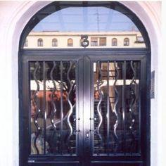 puerta comunidad de hierro rematada en arco