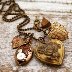 A Heart Locket Charm Cluster #necklace with a brass heart locket mingling with a medley of little charms and curios. #nostalgems #handemadejewelry #jewelry
