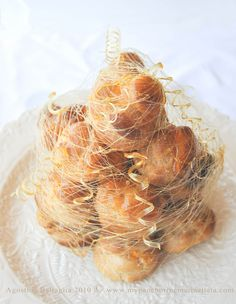 """Piece Montée (""""mounted piece"""") or Croquembouche (""""crunch in the mouth"""").  A high pyramid/cone made of profiteroles (cream-filled puff pastries) sometimes dipped in chocolate, bound with caramel, and usually decorated with threads of caramel, sugared almonds, chocolate, flowers, or ribbons."""