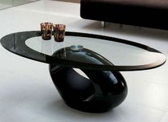 artful coffee table with black base and glass top