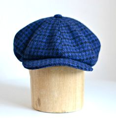 This is a mens Newsboy Hat made with vintage wool in royal blue and black check. This is a lovely medium weight wool for Winter.  The cap is made up of 8 top stitched panels finished with a self covered button. The bill of the cap is reinforced with millinery grade plastic found in commercial hats and can be shaped.  The cap is lined in high quality 100% cotton sateen in black. The cotton has a satin like finish.  The interior is finished with a hand sewn grosgrain ribbon sweatband and…