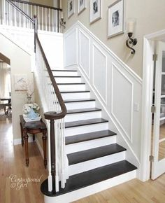 stairs...dark stained steps and railings, white risers, photo wall...