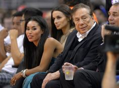 In this photo taken on Friday, Oct. 25, 2013, Los Angeles Clippers owner Donald Sterling, right, and V. Stiviano, left, watch the Clippers p...