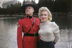 """Sweater girl Monroe, seen here with a real Mountie, photographed by her makeup artist, Allan """"Whitey"""" Snyder, in Banff, Canada, during the filming of the movie River of No Return."""