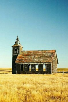 An Old Abandoned Church out in a field.