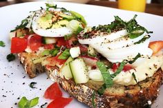 Hummus Toast: Grilled 7 Grain Bread topped with family recipe hummus, chopped organic tomatoes and cucumbers, radishes, scallions, mint, organic hard boiled egg and sumac.