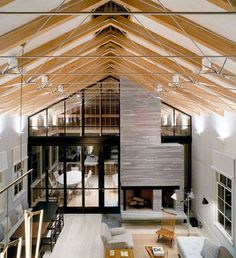 In this rustic barn conversion, Leroy Street Studio sets a traditional environment within an unmistakably modern interior that also channels inside the emotion of Long Island. The main space includes an open living, dining and kitchen hall with a ceiling system composed of wood steel timber frame members below an overhead skylight. A stunning grey stone fireplace divides the main hall space from the outdoor porch. #architecture #design #interiors #interiordesign #longisland