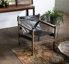cg sparks, black leather sling arm chair, aztec pattern rug, wire plant stand, moroccan tables, concrete floors