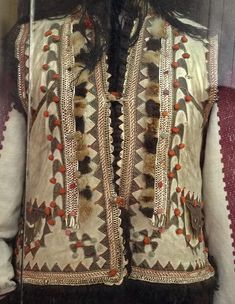 "Traditional female costume from Rakhiv district, Transcarpathian region, the beginning of the 20th century. Close-up view. You can see a lot of decorations that are used to embellish the sleeveless fur coat called ""keptar"": embroidery, leather and fur elements, and tiny yarn pom-pons"