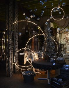 CIRCULAR LIGHT FORMATIONS  Who knew that painting some Hula-Hoops black, wrapping them in lights and hanging them from the ceiling could transform a room into a magical winter art exhibit? Try this for your next holiday party if you really want to impress the guests