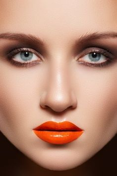 Trendy makeup,consisting of light eyeshadows,little mascara and extremely  bright orange lipgloss 693e3058afa6