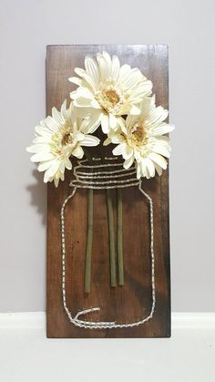 This rustic Mason Jar with flowers in it would be perfect for a rustic themed kitchen or other living areas! This piece was made from nails and string on stained wood, and it was filled with flowers. I can make this with different colored string or even customize it by adding words or a date onto the wood - to customize this piece, go to my page (BoatMade) and order the listing called Custom String Art and write a note to me or send me a message detailing what you would like!  Dimensions: 24…
