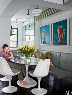 In accessories designer Fiona Kotur's Hong Kong home, James, left, and Rex do homework at the kitchen's Saarinen table, under the gaze of bold and bright Simon Birch oil portraits of their younger brothers | archdigest.com