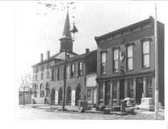 The public ground as seen fronting on West Market St. 1893. The buildings are, left to right, the court house, the fire engine house and judge's office, a small structure of unknown function, and the IOOF Hall incorporating the Odd Fellows Hall upstairs and Neri Hanna's bookstore and a monument shop downstairs.