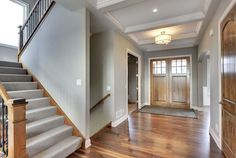 Custom foyer masterfully designed with hardwood flooring, a coffered ceiling and large double doors with windows for natural lighting - 2015 Parade of Homes | Creek Hill Custom Homes MN