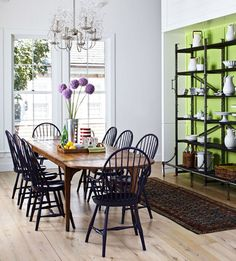 Black windsor chairs at a wood table, green wall and shelves