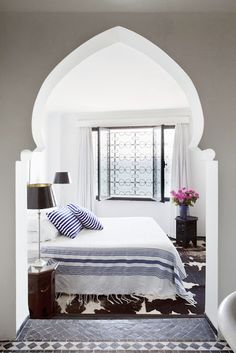 A moroccan bedroom. An animal cow hide rug, blue and white bedding, iron window screen. http://cococozy.com