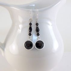 These pretty black and silver #earrings are made with some pretty black and silver dangles.  I attached them to connectors made with black Swarovski bicones, silver spacers ... #jewelry #onfireteam