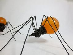 "Single Pumpkin Orange Swirled Spider Repurposed Art. Lurking about is this simplistic, and delicate single spider. She has a beautiful swirled orange colored abdomen. I have a limited number of these left. Her sprawled legs measure about 7"" in diameter. I created her using a vintage acrylic globe and a few lengths of wire. Beware her gaping mandibles.... She can bite if you are not careful! I will make you a spider very similar to this beautiful spider. PLEASE NOTE: This spider is made to..."