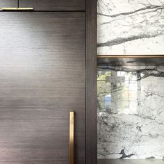 Marble and brass hood detail. Cabinets made of an eco-wood made of reconstituted white oak scraps. Not only is it eco-friendly, but the grain is beautifully consistent.| Canadian interior designer Nam Dang Mitchell