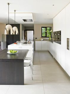 White matt lacquer kitchen with dark stained oak dining table and breakfast cabinets. Wall-mounted appliances and large island with integrated hob. Elegant Kitchens, Bespoke Kitchens, Luxury Kitchens, Cool Kitchens, Modern Kitchens, Grand Kitchen, Luxury Kitchen Design, Open Plan Kitchen, Kitchen Ideas